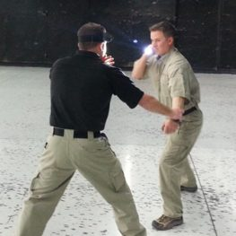 2 People facing each other using a flashlight for self defense